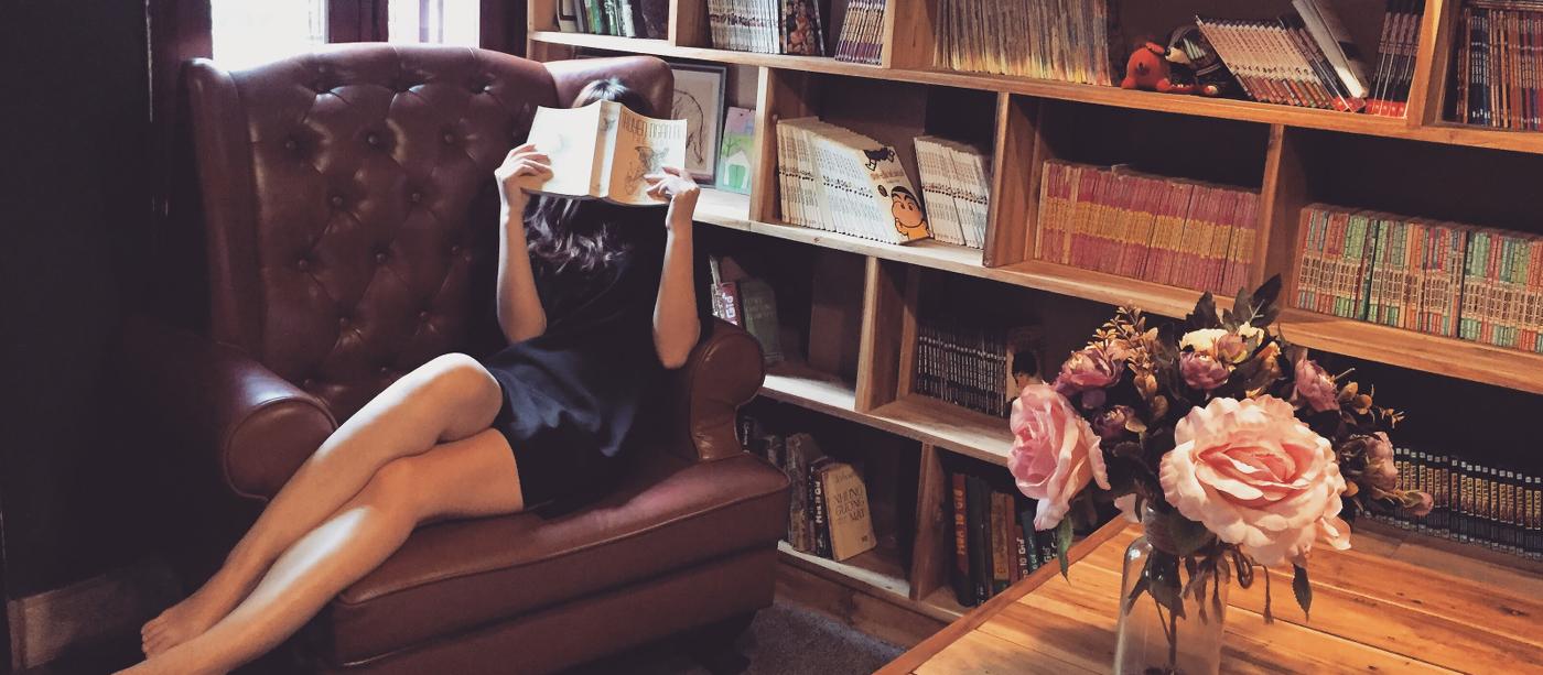 Lesende Frau mit Bücherregal im Hintergrund
